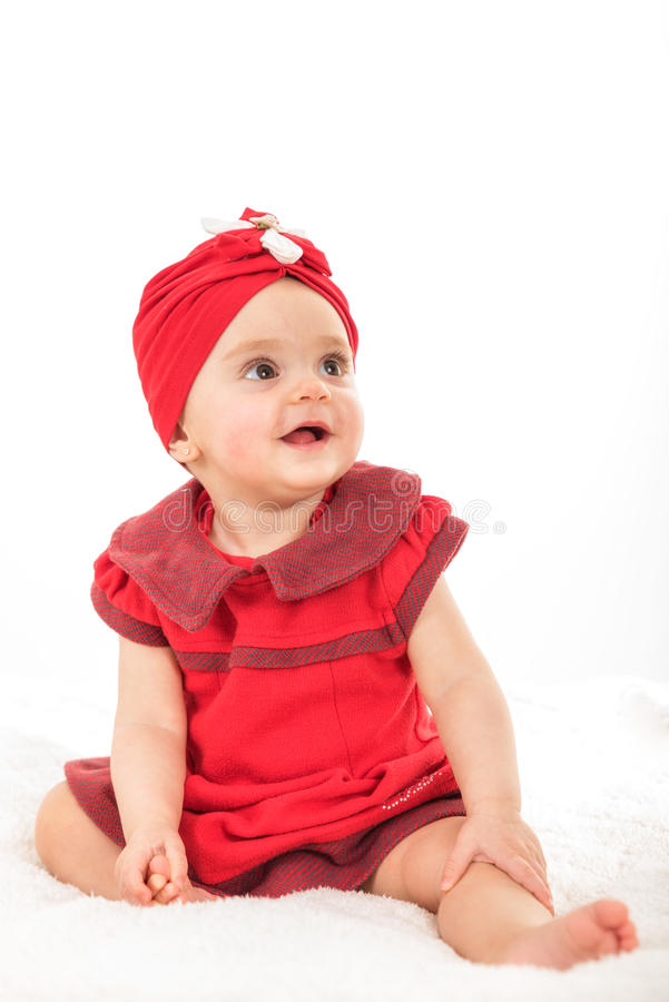 甜女婴画象在红色穿戴了获得乐趣 免版税库存照片