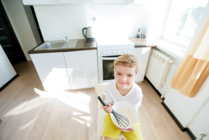 甜学龄前孩子,帮助他的妈妈在厨房里,做薄煎饼早晨,愉快的童年 免版税库存照片