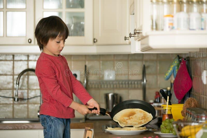 甜学龄前孩子,帮助他的妈妈在厨房里,做pa 图库摄影