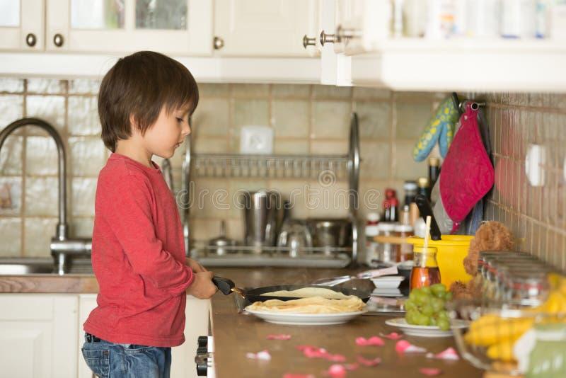 甜学龄前孩子,帮助他的妈妈在厨房里,做pa 库存照片