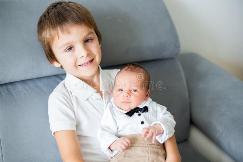 甜学龄前男孩,拥抱与柔软和关心他小 免版税图库摄影