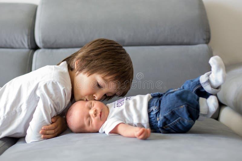 甜学龄前男孩,拥抱与柔软和关心他小 免版税库存图片