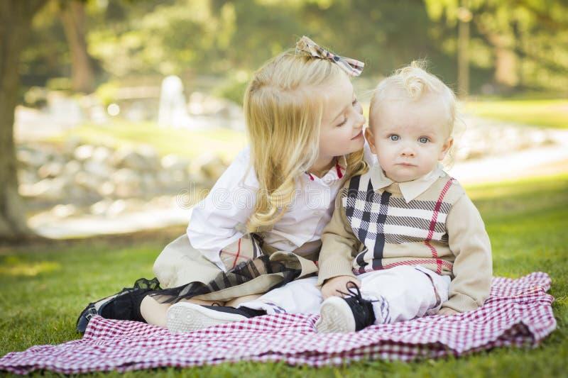 甜小女孩在公园亲吻她的小兄弟 图库摄影