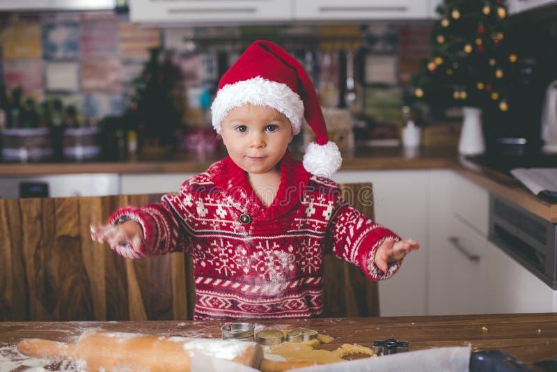 甜小孩孩子和他的哥哥,男孩,在家准备圣诞节曲奇饼的帮助的妈妈 免版税库存照片