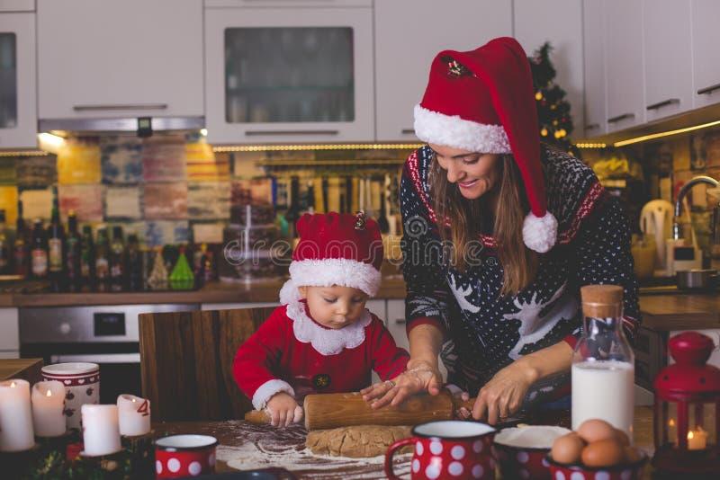甜小孩孩子,男孩,准备圣诞节厨师的帮助的妈妈 免版税库存图片