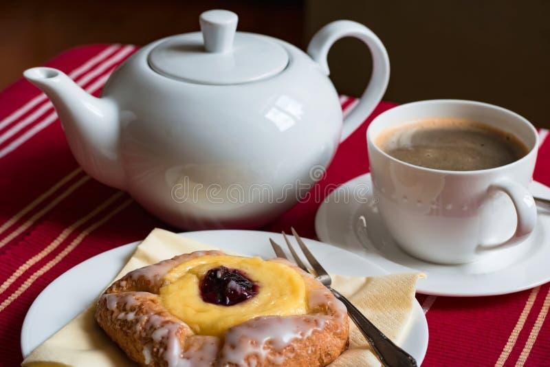 甜断裂:杯子无奶咖啡和酥皮点心充满奶油和果酱在桌上服务 库存照片