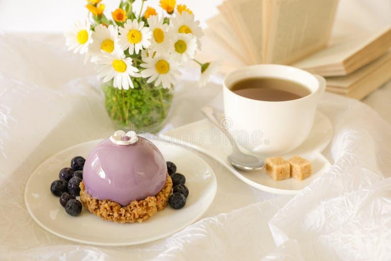 甜早晨早餐时间概念,美丽的紫罗兰色蛋糕,蓝莓,茶在春黄菊附近花束的和打开 免版税图库摄影