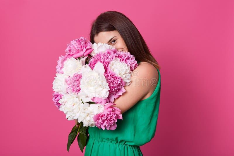 甜有吸引力的女性牡丹藏品巨大的花束画象接近她的,报道她的面孔的大部分用它,看 库存图片