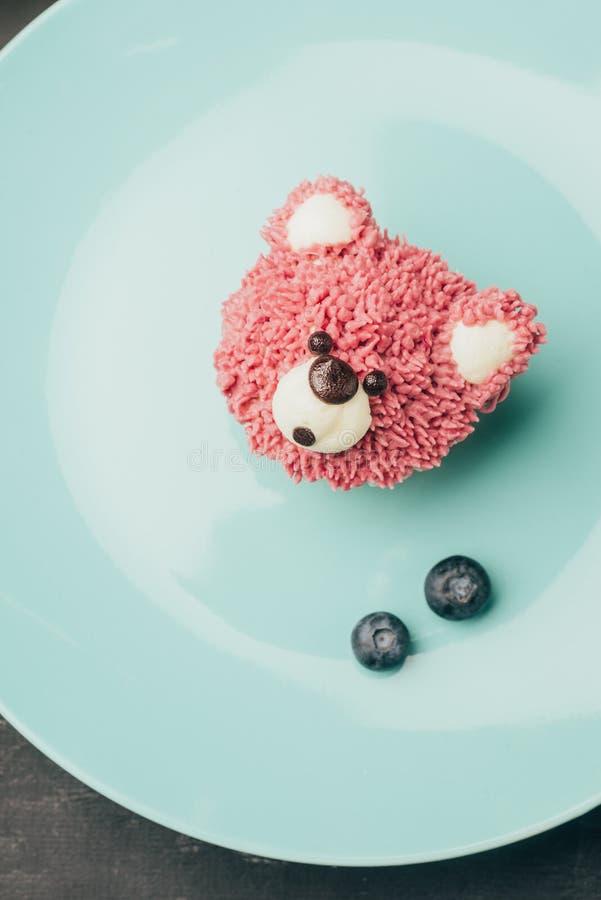甜桃红色松饼顶视图在熊和新鲜的蓝莓形状的  图库摄影