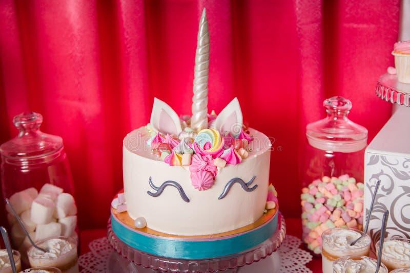 甜桌和大独角兽为女婴第一个生日结块 棒棒糖用很多另外糖果和甜点结块 免版税库存照片