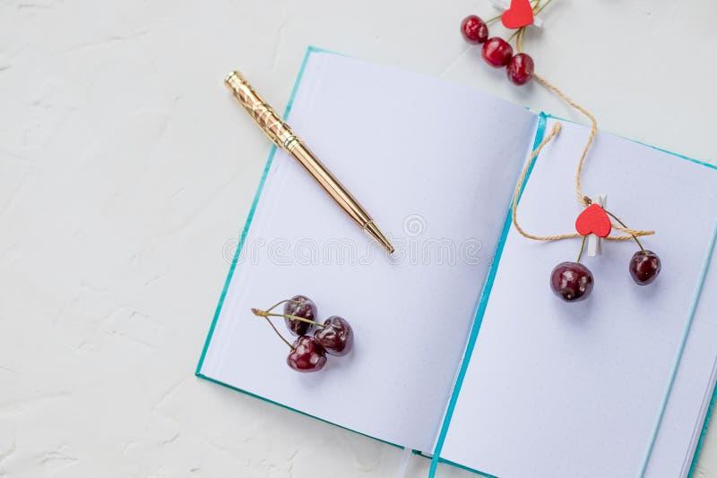 甜樱桃、红色心脏和笔记本与金黄笔 与笔和可爱的红色的Openning笔记本白色空白页 免版税库存图片