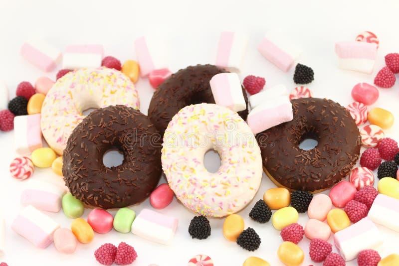 甜油炸圈饼、许多明亮的糖果和蛋白软糖 库存图片