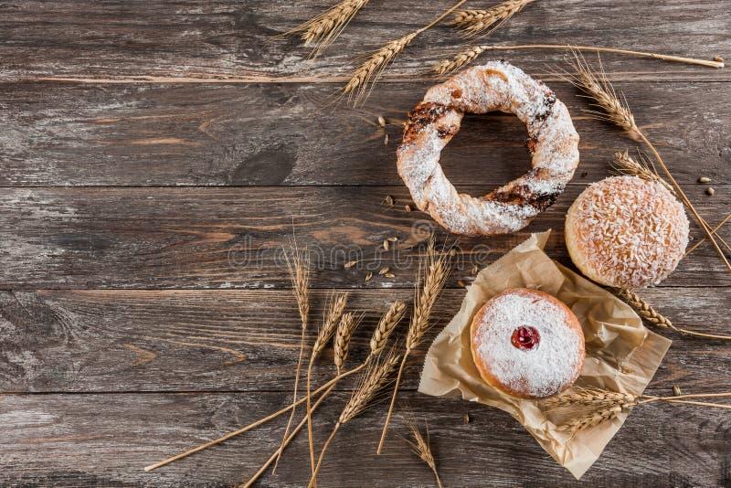 甜油炸圈饼和椒盐脆饼在木背景 鲜美多福饼用果酱,顶视图 免版税库存图片