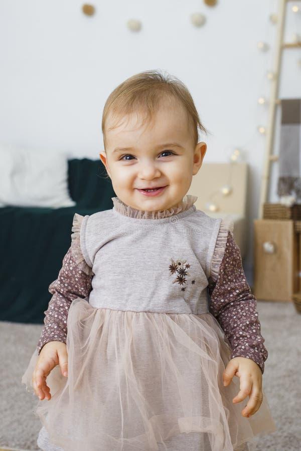 甜点和可爱宝贝女孩的图象礼服的,美丽的1岁微笑的女孩,小孩画象  愉快的子项 库存照片