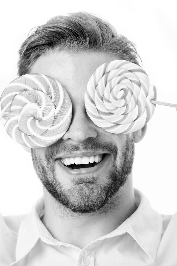 甜点施催眠术的人紧密  铭记事实糖营养 人英俊的有胡子的人拿着棒棒糖糖果 人 免版税图库摄影