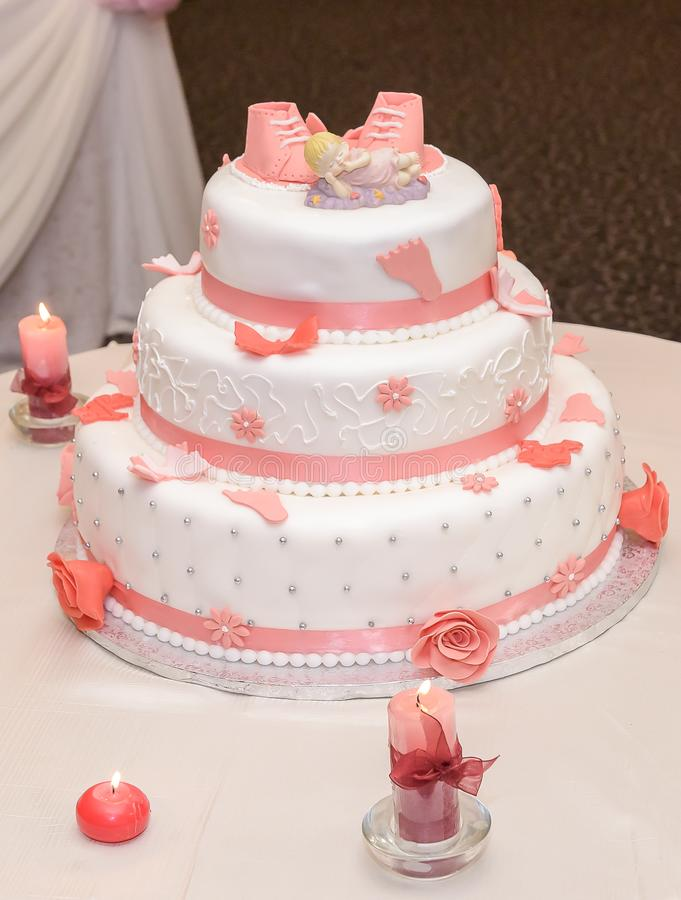 甜点施洗与桃红色糖鞋子和灼烧的蜡烛的蛋糕 免版税库存图片