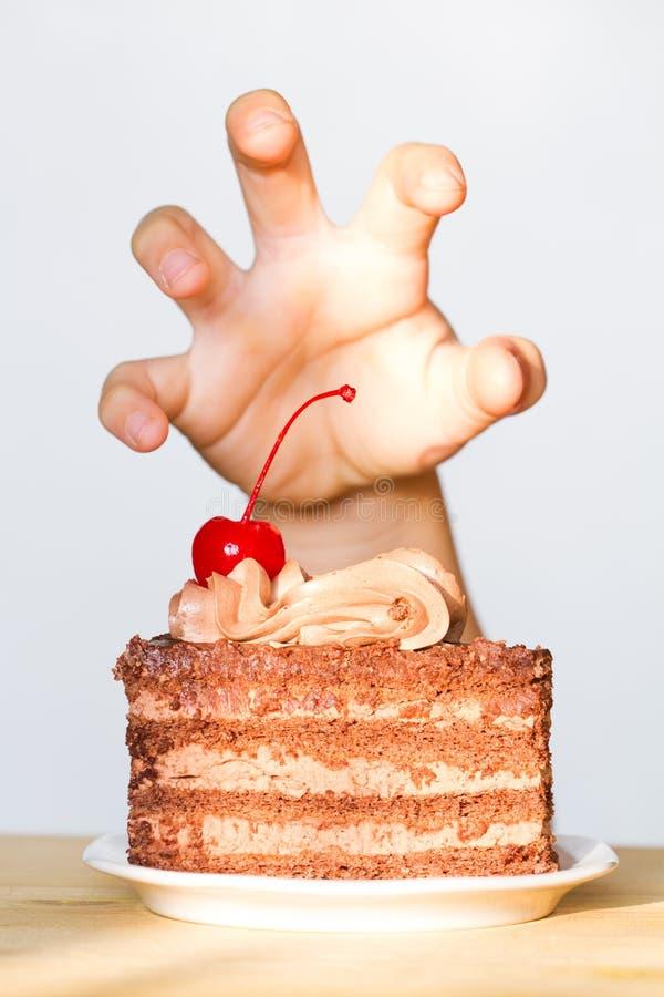 甜点概念的贪婪与手和巧克力蛋糕 库存照片