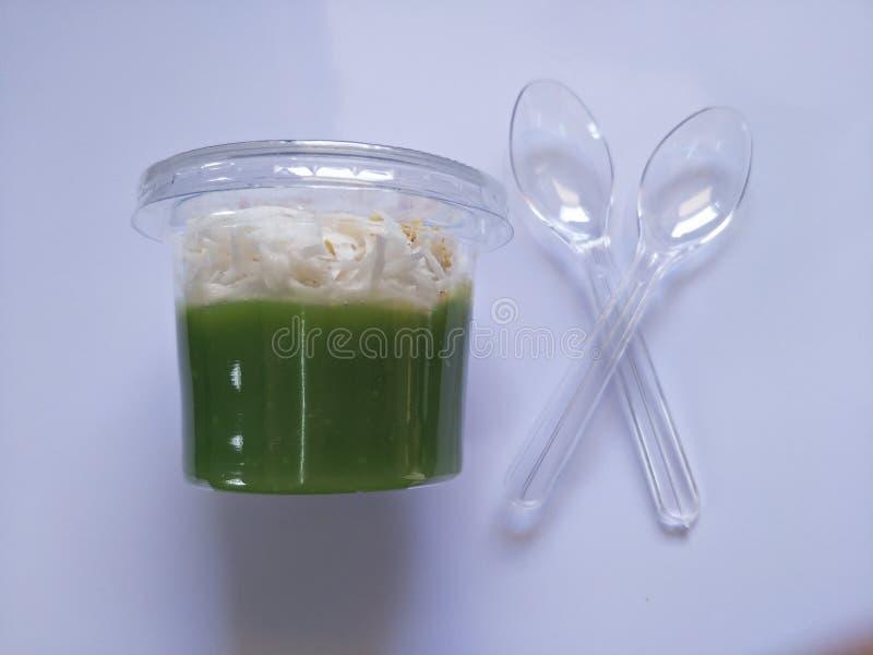 甜点,在玻璃的pandan味道与吃的白色背景一把匙子 图库摄影