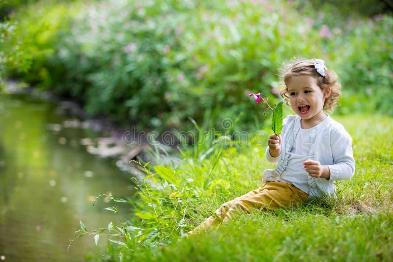 甜点,愉快的小女孩坐草 免版税库存照片
