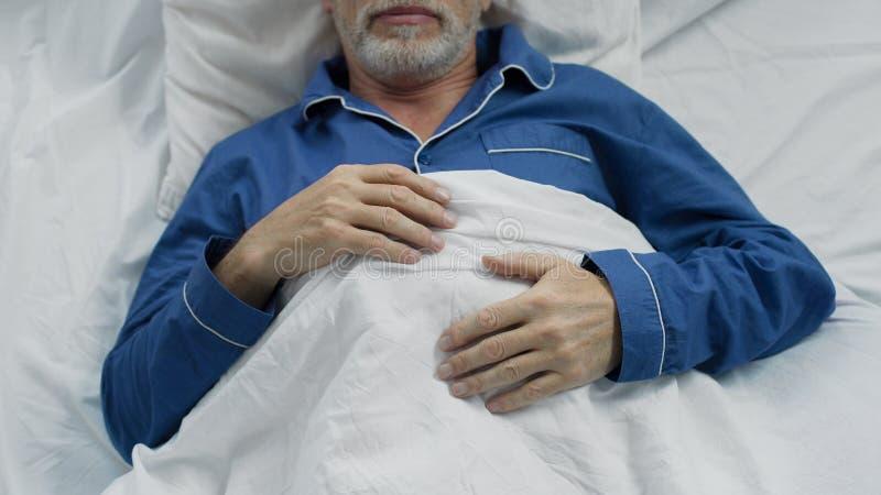 甜甜地睡觉在床上的男性领抚恤金者,享受在矫形床上的舒适 免版税库存照片