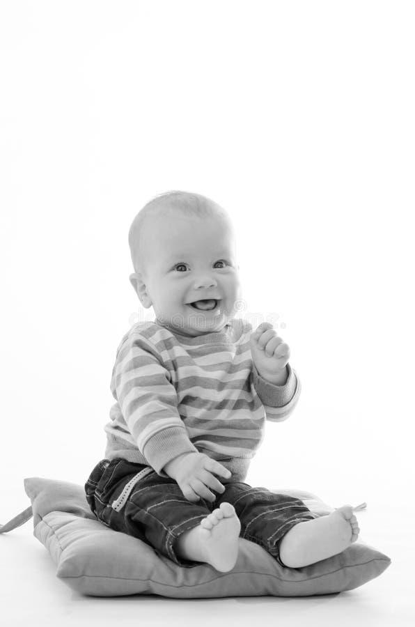 甜男孩婴儿微笑坐在白色b隔绝的绿色枕头 库存图片