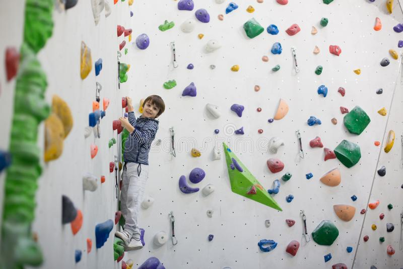 甜矮小的学龄前男孩,上升的墙壁户内 免版税库存照片
