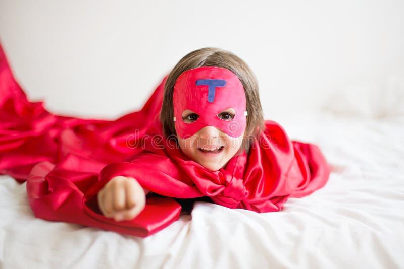 甜矮小的学龄前男孩,在家演奏超级英雄 免版税库存图片