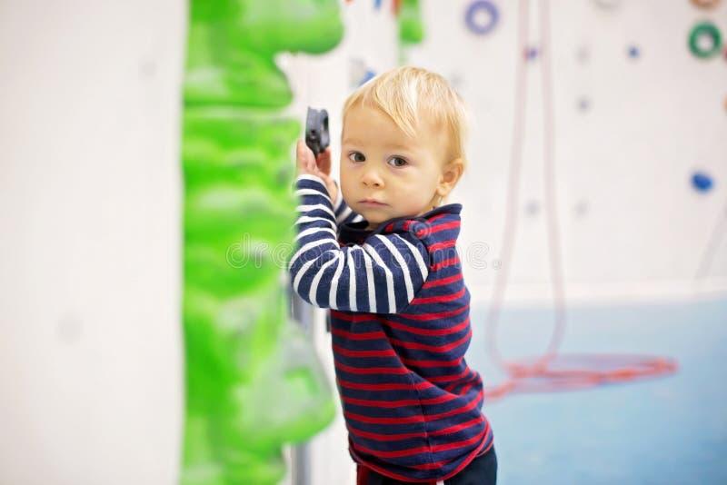 甜矮小的小孩男孩,设法攀登墙壁户内 图库摄影