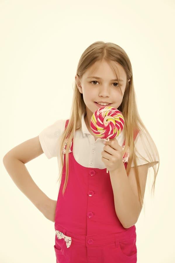 甜神色 女孩吃在白色隔绝的棍子的糖果 与棒棒糖的儿童微笑 愉快的孩子用漩涡焦糖 免版税图库摄影