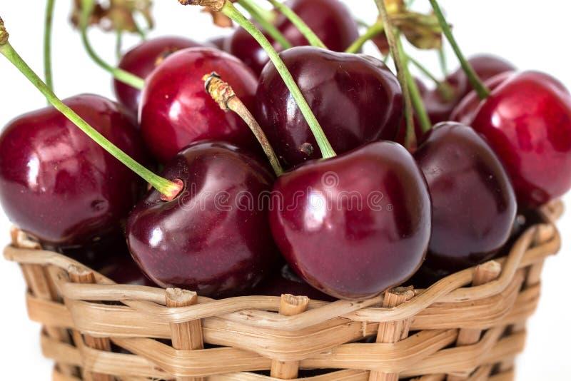 甜红色樱桃充分的篮子在词根关闭的 库存图片