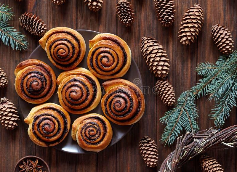 甜自创圣诞节烘烤 与可可粉装填的桂皮卷小圆面包 Kanelbulle瑞典人点心 欢乐的装饰 免版税库存照片