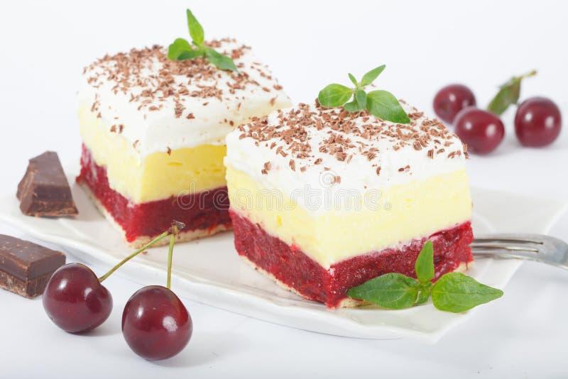 甜自创樱桃蛋糕用香草和纯奶油在白色板材 免版税库存照片