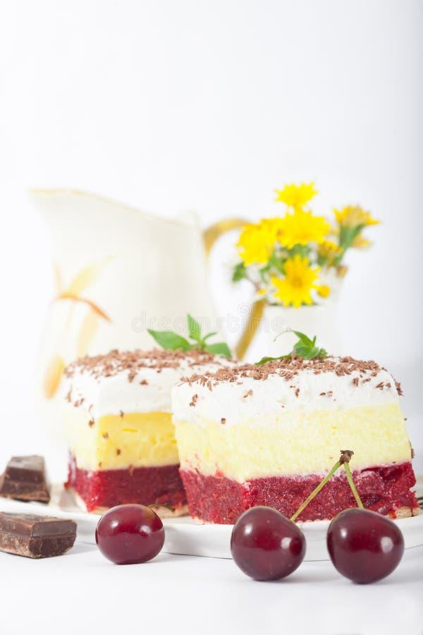 甜自创樱桃蛋糕用香草和纯奶油在白色板材 库存图片