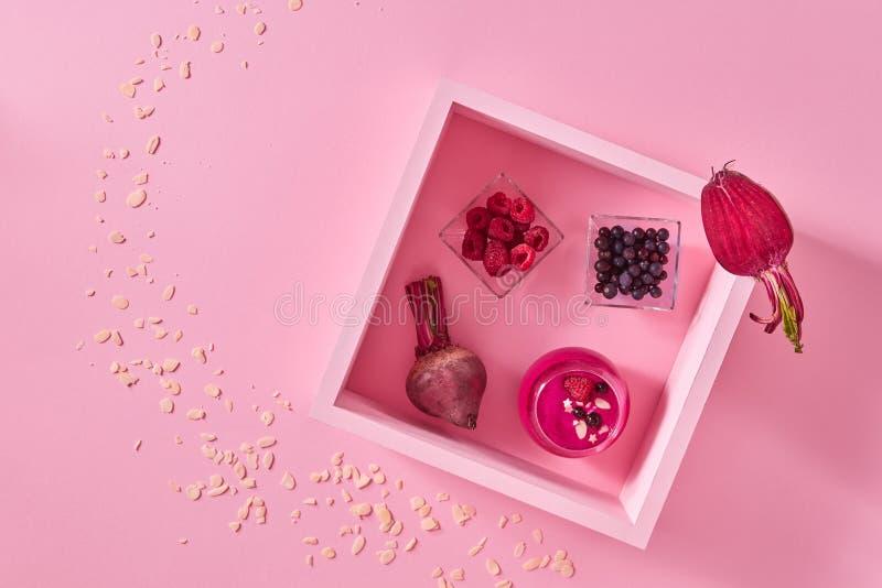 甜菜和莓新鲜的圆滑的人在一个木制框架在桃红色纸背景与拷贝空间 顶视图 免版税库存照片