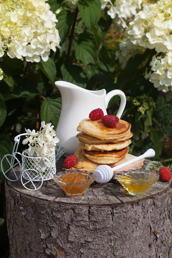 甜薄煎饼早餐在晴朗的庭院里 免版税库存照片