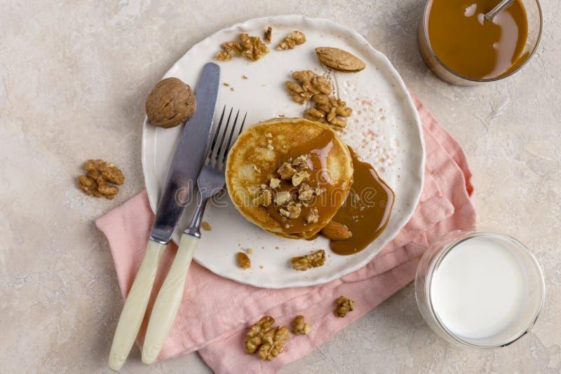 甜薄煎饼用煮沸的浓缩牛奶和核桃在板材有近叉子的和刀子、牛奶在玻璃和焦糖在瓶子,在 免版税库存照片