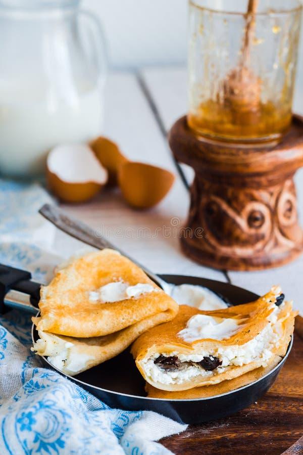 甜薄煎饼用酸奶干酪,修剪,在油煎的p的蜂蜜 免版税库存照片