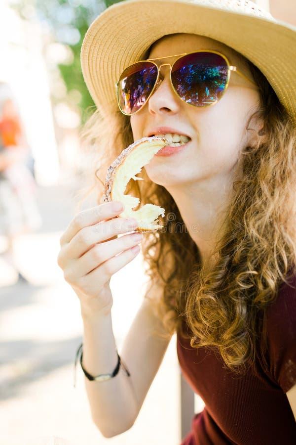 甜蛋糕,女孩吃着Trdelnik片断  免版税库存照片