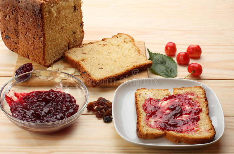 甜面包用葡萄干和杏仁、黄油和樱桃果酱 免版税库存照片