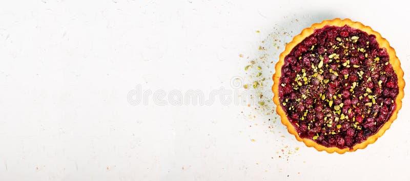 甜馅饼用莓,樱桃,红浆果用开心果,在白色具体背景的搽粉的糖 库存照片