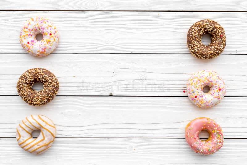 甜鲜美快餐 在白色木背景顶视图拷贝空间的上釉圆环 免版税库存图片