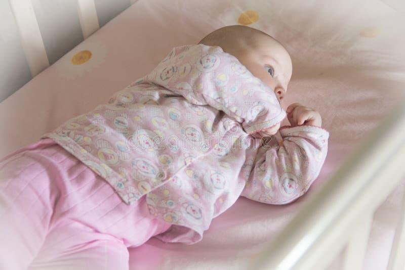 甜婴孩在小儿床在 免版税库存照片