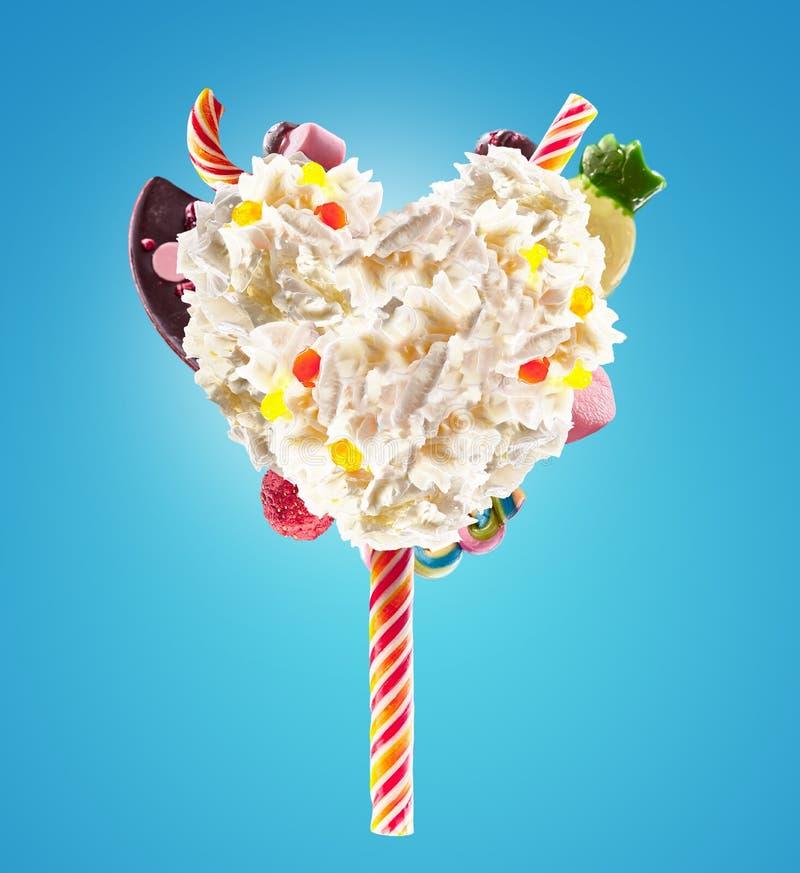 甜Lolipop以打好的奶油的心脏形式与甜点,果冻,心脏正面图的 疯狂的freakshake食物趋向 前面 免版税库存图片