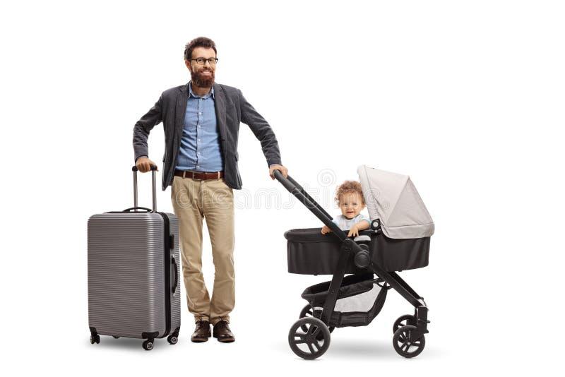 生与一个手提箱和他的小儿子婴儿推车的 免版税库存照片