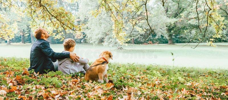 生与与小猎犬狗的儿子步行并且享受温暖的秋天天 免版税库存照片