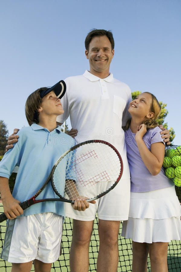 生与儿子和女儿由在网球场画象正面图的网 图库摄影