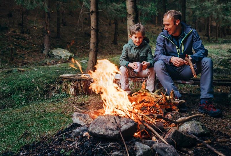 生与儿子温暖的近的营火,喝茶并且有conversat 免版税库存图片
