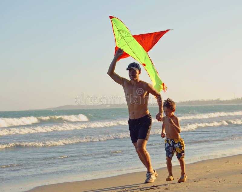 生与儿子,在海岸的日落与风筝,愉快的家庭 库存照片