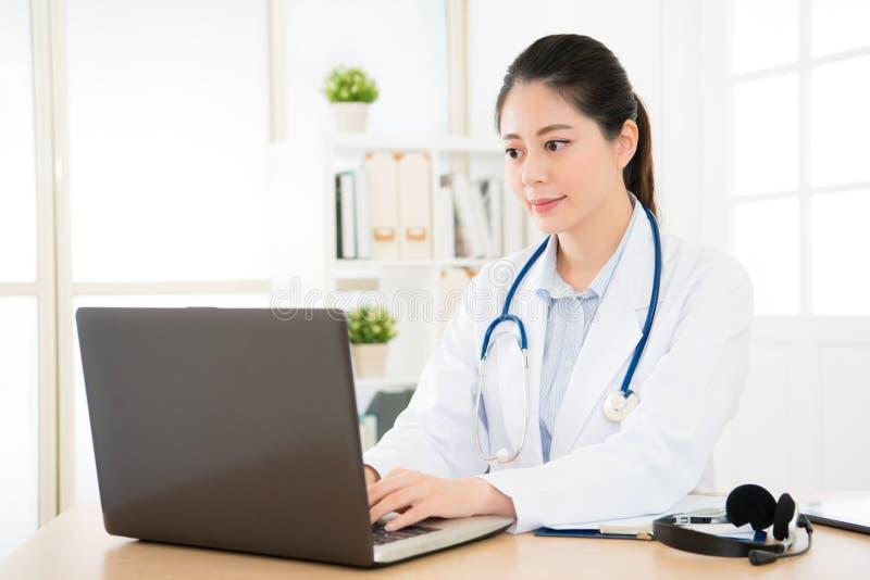 医生与她的计算机一起使用 免版税库存图片
