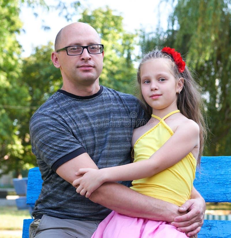 生与孩子在公园,愉快的家庭画象,两人坐长凳,育儿概念 免版税库存照片